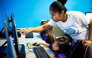 volunteer helping a child on the computer