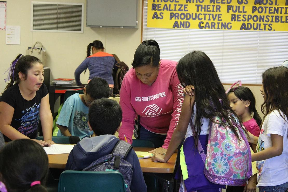 volunteer helping children in a classroom